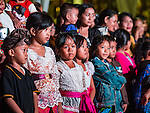 14 JULY 2016 - UBUD, BALI, INDONESIA: Children watch a traditional Balinese legong dance troupe perform during the mass cremation ceremony in Ubud. Local people in Ubud exhumed the remains of family members and burned their remains in a mass cremation ceremony Wednesday. Thursday was spent preparing for Saturday's ceremony that concludes the cremation and included traditional Balinese Legong dances performed in the evening. Almost 100 people will be cremated and laid to rest in the largest mass cremation in Bali in years this week. Most of the people on Bali are Hindus. Traditional cremations in Bali are very expensive, so communities usually hold one mass cremation approximately every five years. The cremation in Ubud will conclude Saturday, with a large community ceremony.   PHOTO BY JACK KURTZ