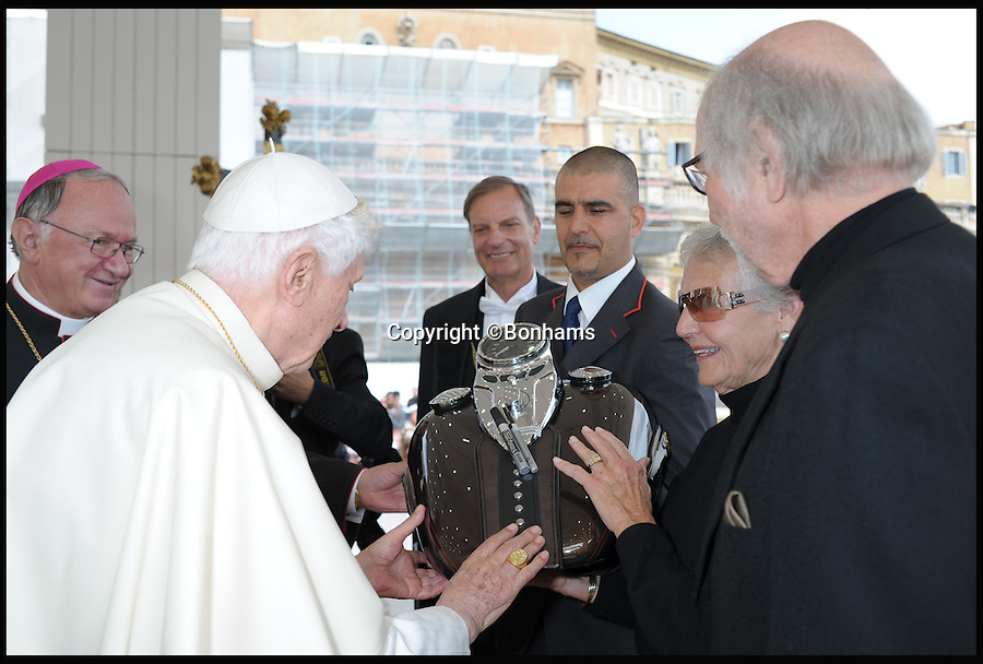 BNPS.co.uk (01202 558833)<br /> Pic: Bonhams/BNPS<br /> <br /> ***Please Use Full Byline***<br /> <br /> Pope Benedict being presented with the Harleys fuel tank.<br /> <br /> Holy Davidson - Twin Pope.<br /> <br /> A unique and historic motorbike is being sold by Bonhams next month -  A Harley Davidson Softail Classic that carries the signature of Pope Benedict XVI, and was later presented to his successor Pope Francis. <br /> <br /> The Papal abdication makes this stunning machine historically unique and despite its £20,000 estimate bidding is likely to be fierce.<br /> <br /> This most holy of Harley's is unlikely to attract much interest from the famous American brands most loyal fans though - Hells Angels.<br /> <br /> Bonhams 5th Feb - Paris - Est £20,000