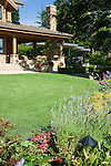 lavender plants and a mixed border occupy the foreground while the covered patio entertaining area of a large estate size home sits in a soft focus background behind a perfect green lawn