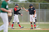 Edgewood Eagles head coach Al Brisack fist bumps Bryan Sternig (1) during a game against the Babson Beavers on March 18, 2019 at Lee County Player Development Complex in Fort Myers, Florida.  Babson defeated Edgewood 23-7.  (Mike Janes/Four Seam Images)