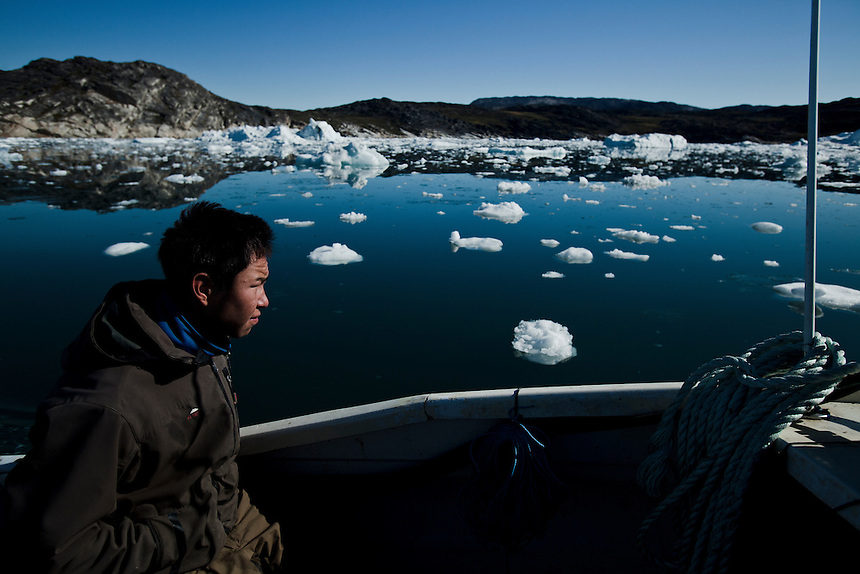 A young Inuit fisherman travels between towns on the remote coastline of West Greenland, August 2011. Photo: Ed Giles.
