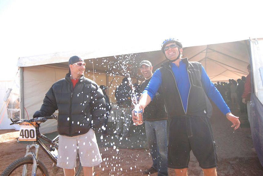 Participants in the 2007 24 hours of Moab mountain bike race celebrate finishing the race with a beer.
