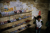 Shoppers walk past a display of shoes for sale in the central market in Xinjie, Yuanyang County, Yunnan Province, China.