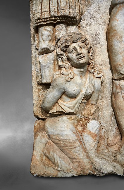 "Roman Sebasteion relief  sculpture of the Emperor and Roman People, Aphrodisias Museum, Aphrodisias, Turkey.  Against a grey background.<br /> <br /> The emperor is a naked warrior and is crowned by a personification of the Roman People or the Senate wearing a toga, the stately civilian dress of a Roman Citizen. The crown is an oak wreath, the corona civica or ""civic crown"" awarded for saving citizens lives. The emperor is setting up a battlefield trophy beneath which kneels an anguished barbarian women captive"