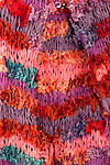 Knotted Silk 01 - Detail of red, pink and mauve tied and knotted silk wrap.