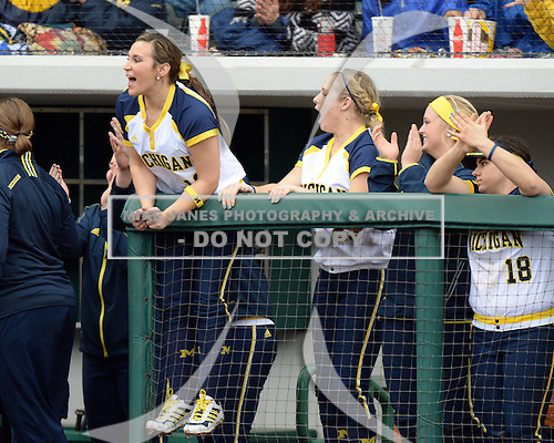 Michigan Wolverines players including outfielder Kelly Christner (21) cheer on their teammates during the season opener against the Florida Gators on February 8, 2014 at the USF Softball Stadium in Tampa, Florida.  Florida defeated Michigan 9-4 in extra innings.  (Copyright Mike Janes Photography)