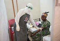 "Tenneh Kennedy, R.N. checks on unconfirmed Ebola patient Lorpu Melbah in the ""red zone"" of the ELWA II ETU in Paynesville, Monrovia, Liberia on Monday, March 9, 2015.  Melbah tested negative for Ebola.<br /> Kennedy wears a sticker with her portrait on her PPE, part of Occidental College professor Mary Beth Heffernan's PPE Portrait project she has been working on in Liberia. PPE (personal protective equipment) is mandatory for all staff while working in the area with patients, called the ""red zone."" The area is isolated and staff only enter to care for patients at designated times throughout the day, which means human contact for patients is minimal.<br /> (Photo by Marc Campos, Occidental College Photographer) Mary Beth Heffernan, professor of art and art history at Occidental College, works in Monrovia the capital of Liberia, Africa in 2015. Professor Heffernan was there to work on her PPE (personal protective equipment) Portrait Project, which helps health care workers and patients fighting the Ebola virus disease in West Africa.<br />