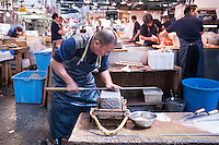 A man works at a whetstone sharpening knives at Tsukiji Fish Market, Tokyo, Japan.