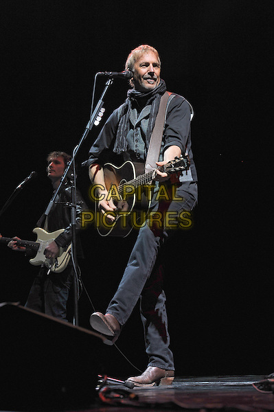 Kevin Costner & Modern West.Live in concert, Saint Petersburg, Russia, April 11th 2013..on stage gig music performing full length grey gray black top waistcoat scarf shirt guitar playing leg kicking microphone .CAP/PER/VB.©VB/PersonaStars/CapitalPictures
