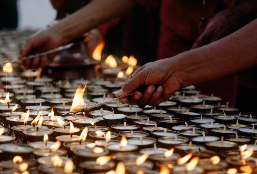 Buddhist Monks light PUJA CANDLES at BODHANATH STUPA - KATHAMANDU, NEPAL