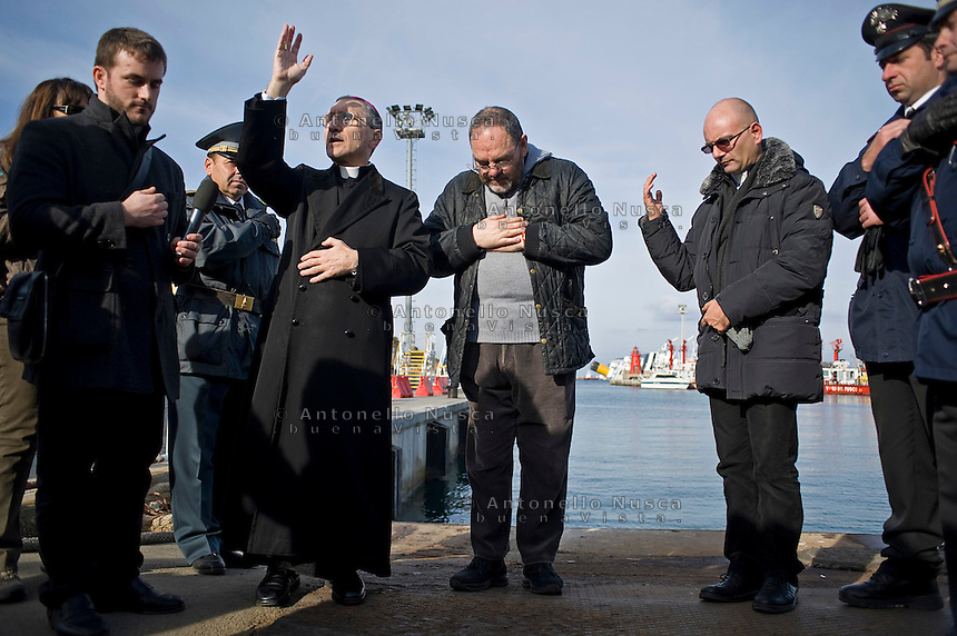 Isola del Giglio, Italy, January 19, 2012. The bishop of Oebetello, Girolamo Borghetty (L) blesses the cruise liner Costa Concordia aground in front of the harbour of the Isola del Giglio (Giglio island) after hitting underwater rocks.