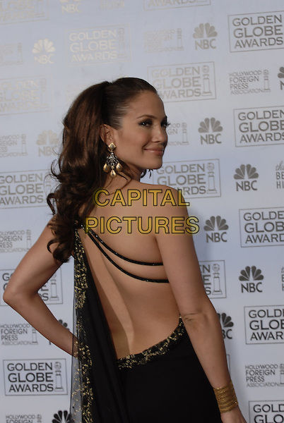 "JENNIFER LOPEZ.Pressroom - 64th Annual Golden Globe Awards, Beverly Hills HIlton, Beverly Hills, California, USA..January 15th 2007. .globes press room Marchesa half one shoulder gold pattern black earrings dress straps hand on hip bracelets looking over shoulder.CAP/AW.Please use accompanying story.Supplied by Capital Pictures.© HFPA"" and ""64th Golden Globe Awards"""