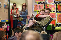 NWA Democrat-Gazette/BEN GOFF @NWABENGOFF<br /> Myra Cooper, 7, sits with her father Staff Sgt. William Cooper of Bentonville Monday, May 8, 2017, with her mother Kelsey Kennedy (left) and stepmother Melissa Cooper looking on, as he reads to her first grade classroom at Apple Glen Elementary School in Bentonville. Each week a parent comes in as a 'Mystery Reader' for their child's classroom at the school, with students receiving clues as to who it will be throughout the week. This week Myra was surprised by her father, who has been away from his family for over a year on deployment to Kuwait with the U.S. Army 77th Combat Aviation Brigade. Staff Sgt. Cooper read to the class from 'Harold and the Purple Crayon' by Crockett Johnson before taking Myra and the rest of their family to spend the day a the nearby Scott Family Amazeum.