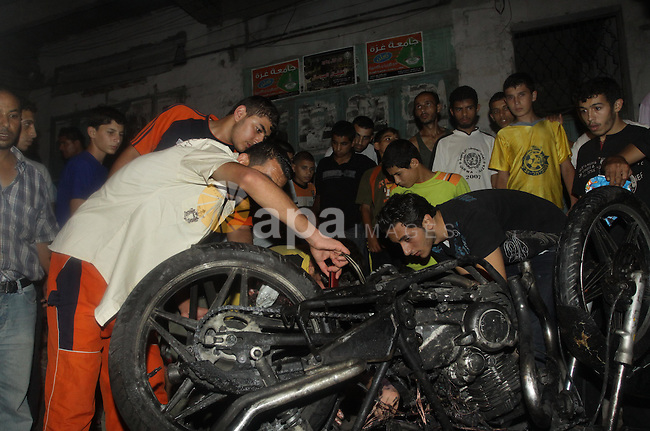 Palestinians inspect a destroyed motorcycle following an Israeli airstrike killing three Palestinian who were riding it, at the main road in Gaza City, Friday, Aug. 19, 2011. Palestinian official said that Dr. Monzer Qrakea, 35, and his brother Motaz, 23, and his son Islam, 5, were killed while they riding a motorcycle in Gaza city. Photo by Naaman Omar