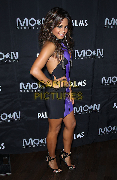 Christina Milian (wearing Lisa Marie Fernandez) .Christina Milian hosts at Moon Nightclub inside the Palms Casino Resort,.Las Vegas, Nevada, USA, .7th January 2012..full length purple black sleeveless dress hand on hip zip up open toe sandals side.CAP/ADM/MJT.© MJT/AdMedia/Capital Pictures.