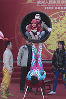 A Chinese acrobat balances a Western mother and her child sitting inside a giant ceramic basin during a performance at a temple fair to celebrate the Lunar New Year of the Tiger on February 15, 2010 in Beijing, China.