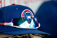 South Bend Cubs hat sits on top of a glove in the dugout during the game against the Lake County Captains on May 30, 2019 at Four Winds Field in South Bend, Indiana. The Captains defeated the Cubs 5-1.  (Andrew Woolley/Four Seam Images)