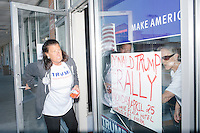 On a window of the state headquarters of Republican presidential candidate Donald Trump's campaign, supporters Anne Corbo, of Scituate, Rhode Island, (right) and Daphne Papp, of Annisquam, Mass., put up a sign for the candidate's speech in Warwick the next day. The two are seen here on Sun., Apr. 24, 2016. The campaign office is located at the Airport Plaza strip mall in Warwick, Rhode Island. The campaigns of Trump, Cruz, and Kasich, have set up their state operations in the same strip mall.