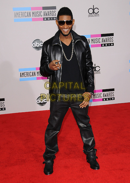 USHER (USHER RAYMOND) .At The 2010 American Music  Awards held at Nokia Theatre L.A. Live in Los Angeles, California, USA,.November 21st 2010..amas arrivals full length jacket trousers finger pointing gesture black sunglasses beard facial hair leather smiling silver necklace chain .CAP/RKE/DVS.©DVS/RockinExposures/Capital Pictures.