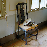 In the dining room of this country house the face and workings of an old clock have been left on an antique chair