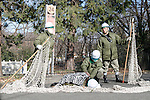 Zookeepers guard an injured staff during an Escaped Animal Drill at Tama Zoological Park on February 7, 2017, Tokyo, Japan. The annual escape drill is held in Tokyo zoos for zookeepers to practice how they would need to react in the event of a natural disaster or another emergency. This year a member of staff wearing a chimpanzee costume was captured and subdued by other zookeepers before it could escape out onto the streets of Tokyo. During the drill, participants used large nets, sticks and tranquilizer guns to make sure the monkey didn't get away. (Photo by Rodrigo Reyes Marin/AFLO)