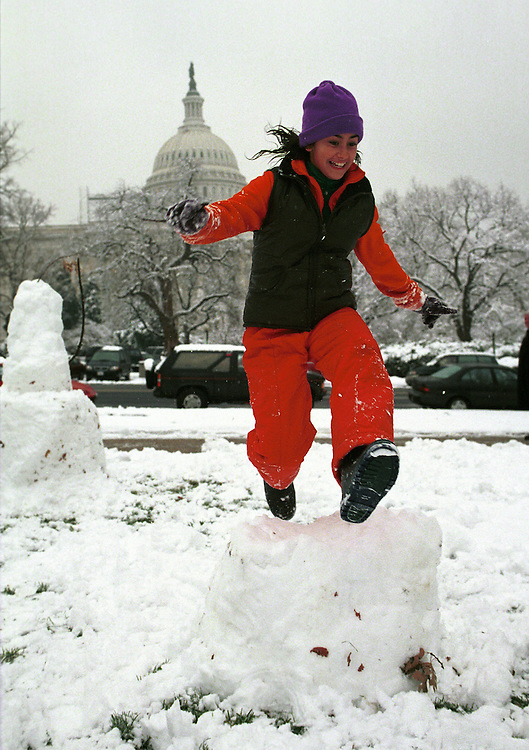 RC20000120-120-TW:01/20/00: Alexi-Noelle O'Brien-Hosein jumps over a toppled snowman in Capitol Plaza on the North side of the Senate.      .       Tom Williams/Roll Call