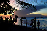 TANZANIA Zanzibar, Stone town, Livingstone beach restaurant and bar, evening at sea, tourist in bar, woman taking a photo of sunset and street hawker selling clothes / TANSANIA Insel Sansibar, Stonetown, abends am Meer, Livingstone beach restaurant and bar