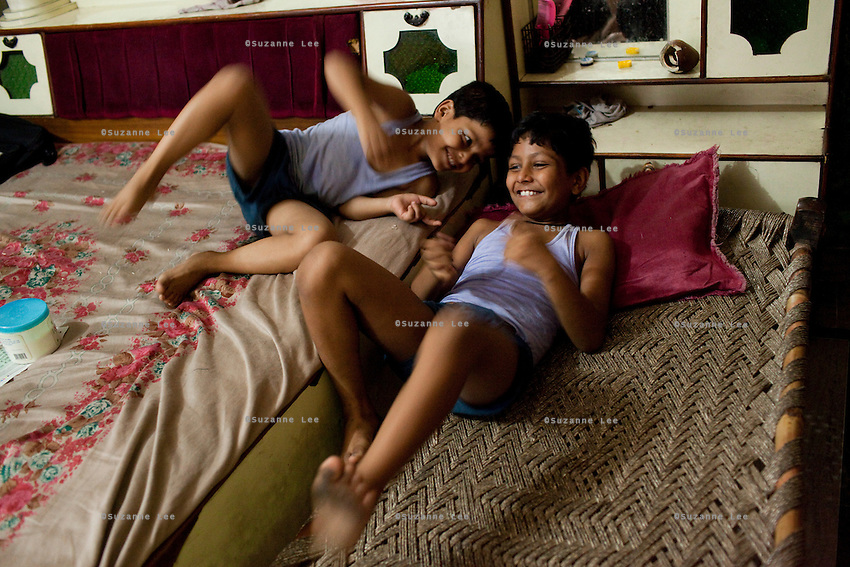 Seema Gupta's children aged 8 and 10 play in their shophouse in Ghaziabad, Uttar Pradesh, India. Seema Gupta, aged 34 (unseen), had a tubectomy done on 9 June 2011 for family planning while her husband, Ramesh Chandra Gupta, aged 38 (unseen), wasn't aware of the option and benefits of non-scalpel vasectomy (NSV). They run a roadside sweets shop at the front of their house and chose to have a family planning surgery done as they did not want to compromise the quality of life for their two children. While Ramesh wanted only 1 child, both his mother and Seema pushed for a 2nd child. Photo by Suzanne Lee / Panos London
