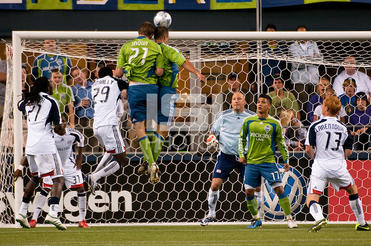 Nate Jaqua (21)  and Patrick Ianni (c) of the Seattle Sounders go for a double header against goalkeeper Matt Ries (3r) and Kenny Mansally (3L) of the New England Revolution in the match at the XBox Pitch at Quest Field on August 20, 2009. The Revolution defeated the Sounders 1-0.