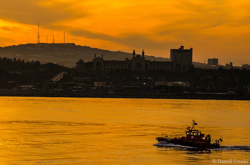 Fine Art Landscape Photograph. <br /> Golden sunset on the Bosphorus Strait in Istanbul, Turkey.<br /> The warm golden rays of the sun highlight a boat that is sailing on the Bosphorus Strait in Istanbul. <br /> The expansive skyline is lined with dramatic golden clouds.