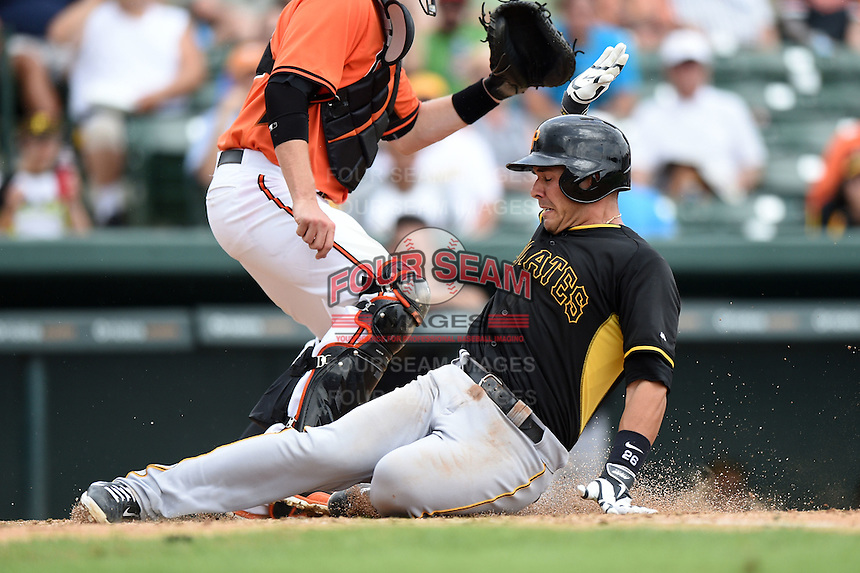 Catcher Tony Sanchez (26) of the Pittsburgh Pirates slides into home during a spring training game against the Baltimore Orioles on March 23, 2014 at McKechnie Field in Bradenton, Florida.  Baltimore and Pittsburgh played to a 7-7 tie.  (Mike Janes/Four Seam Images)