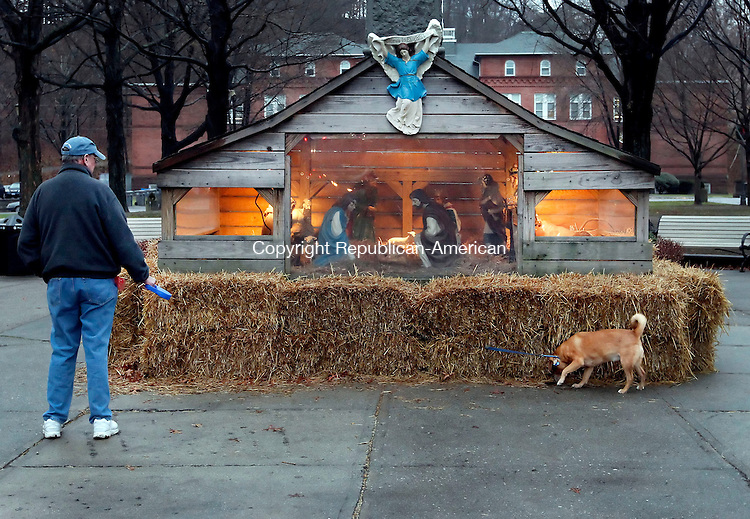 Naugatuck, CT-10 December 2012-121012CM13-  Don Miller of Naugatuck checks out the nativity scene along with his 6 year old Corgi/Beagle mix, Ginger, 6, on the Naugatuck Town Green Monday afternoon.  Miller and his rescue pooch were out enjoying the green despite the rainy afternoon.  According to the National Weather Service, today is expected to mostly cloudy, then gradually becoming sunny, with a high near 48.   Christopher Massa Republican-American