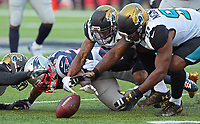 Jacksonville Jaguars A.J. Bouye (21) and Yannick Ngakoue (91) attempt to recover a football fumbled by New England Patriots running back James White (28) in the AFC Championship game Sunday, January 21, 2018 in Foxboro, MA.  (Rick Wilson/Jacksonville Jaguars)