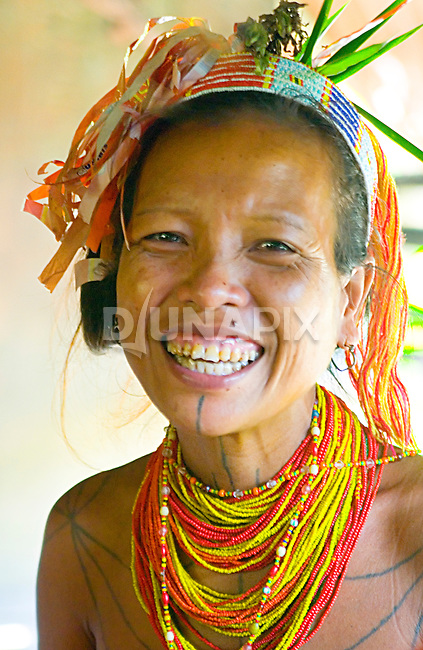 The wife of Sikerei (Shaman) Agoy in Malagassat village, Siberut island, Sumatra, beams a huge smile. She's just returned from a ceremony in a neighboring village, and is thrilled to be wearing a head dress made of a red and yellow instant noodle package she found there.