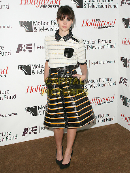Felicity Jones.'Reel Stories, Real Lives' Celebration of the Motion Picture & Television Fund' 90 Years of Service to the Community and Recognizes The Hollywood Reporter's Next Generation Class of 2011 held at Milk Studios in Los Angeles, California, USA..November 5th, 2011 .full length top skirt  shiny pvc leather beige pockets black crochet collar white stripe fringe bangs hair                                       .CAP/RKE/DVS.©DVS/RockinExposures/Capital Pictures.