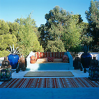 An outdoor living room complete with a built-in sofa and Moroccan cushions, rugs and lanterns