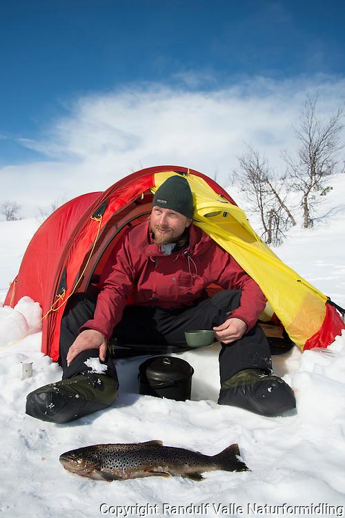 Mann med kaffekopp i telt en varm vårdag. ---- Man drinking coffe in tent a warm spring day.
