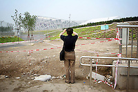 """CHINA. Beijing. A tourists taking a picture of the new Olympic park. In recent years construction has boomed in Beijing as a result of the country's widespread economic growth and the awarding of the 2008 Summer Olympics to the city. For Beijing's residents however, it seems as their city is continually under construction with old neighborhoods regularly being razed and new apartments, office blocks and sports venues appearing in their place. A new Beijing has been promised to the people to act as a showcase to the world for the 'new' China. Beijing's residents have been waiting for this promised change for years and are still waiting, asking the question """"Where's the new Beijing?!"""". 2008."""