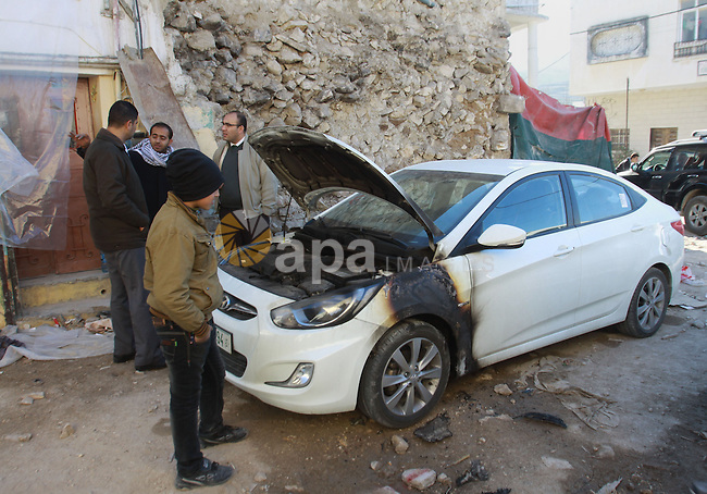 Palestinians look at destroyed vehicle in the village of Madama, on January 8, 2014, the day after Palestinians beat and detained several Israeli settlers who had entered the village of Quasra near the West Bank city of Nablus. Palestinian security sources told AFP locals had apprehended the settlers, some of whom were masked, after earlier clashes between the sides near Qusra village. Photo by Nedal Eshtayah