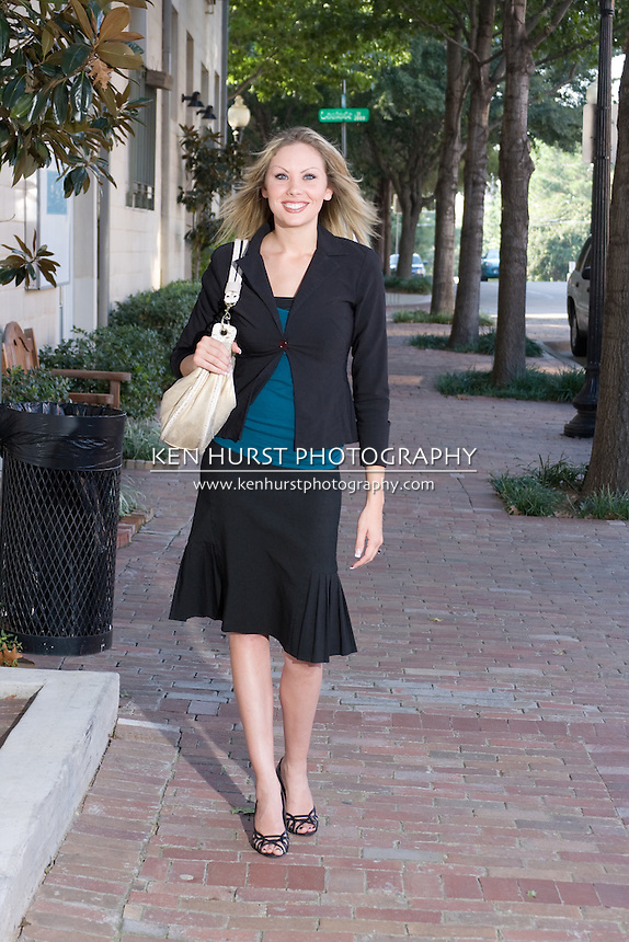 Young business woman strolling along a sidewalk in an urban area.