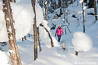 Woman snowshoeing in deep snow in the wintery forest.