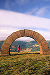 Andy Goldsworthy's Striding Arches sculptures on Bail Hill looking up Dalwhat glen to Cairnhead hill walker walking through arch Dumfries and Galloway Scotland UK