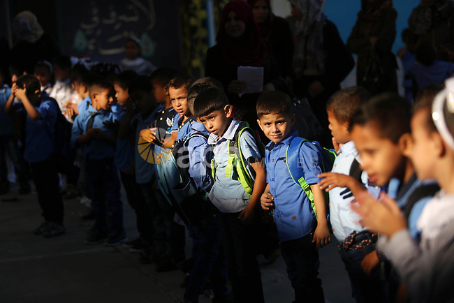 Palestinian schoolchildren stand outside their classrooms on the first day of a new school year, at a United Nations-run school in Deir al-Balah refugee camp in the central Gaza Strip August 23, 2017. Photo by Ashraf Amra