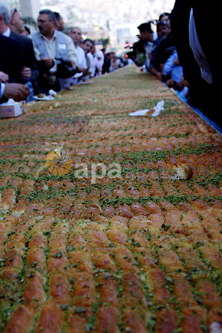 """Palestinians eat of the biggest dish of traditional sweets """"Konafa"""" into the Guinness Book of Records in the West Bank city of Nablus on July 18 2009. Photo by Issam Rimawi"""