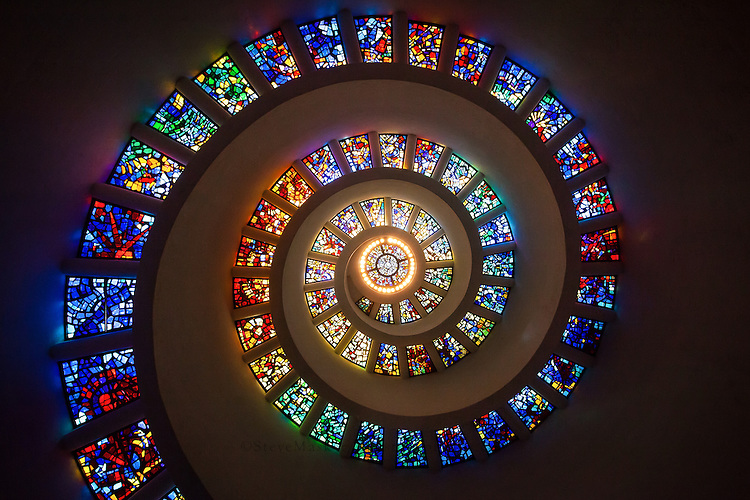 "The most prominent and recognizable feature of Thanks-Giving Square is the Chapel of Thanksgiving, a small, spiral tower that features an enclave for prayerful thanks. The entrance to the chapel is at the end of a 125-foot bridge that runs over a cascading waterfall. Inside the chapel, the spiral is topped with stained glass ""Glory Window"", one of largest horizontally mounted stained-glass pieces in the world. The window was designed by Gabriel Loire of Chartres, France to feature brighter colors as the spiral reached its apex, becoming brighter as it reaches the center. The etched glass window ""The Spirit of Thanksgiving,"" designed by glass engraver John Hutton, features a dove over the doorway."