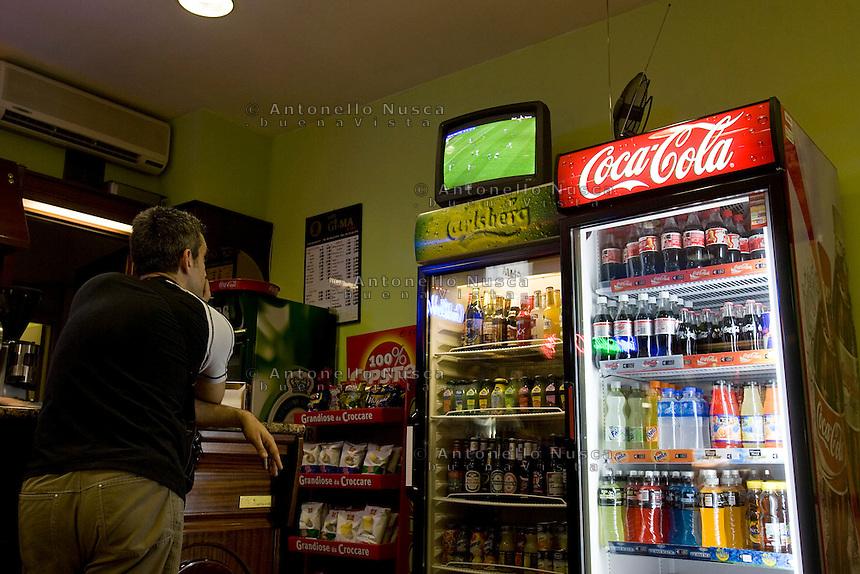 Un tifoso di calcio segue una partita dei campionati del mondo di calcio Germania 2006 sul televisore di un bar.