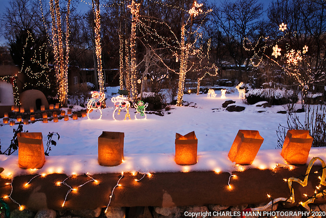 Paper bag faralitos and twinkling lights in the trees surround a display on Canyon Road during the annual Christmas Eve celebration in Santa Fe, New Mexico
