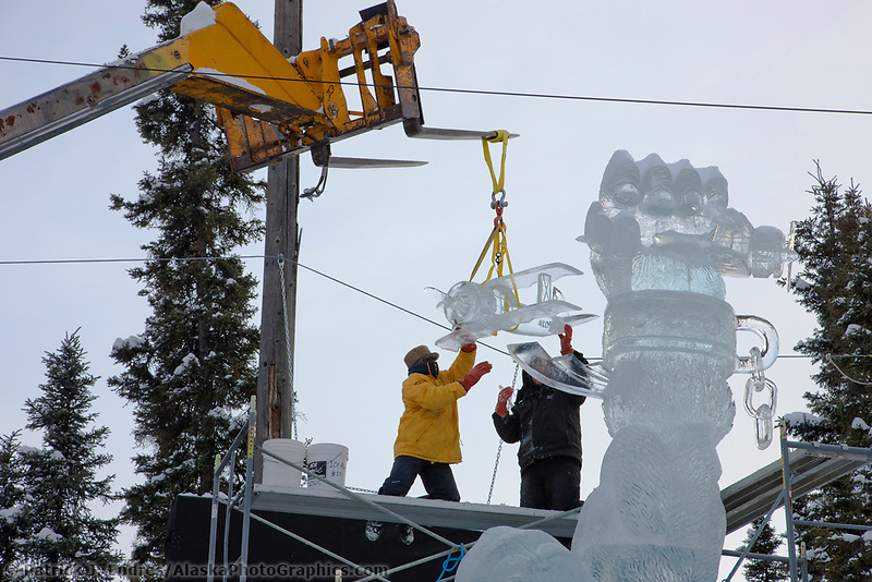 "Team members  hoist a small plane to be placed on the top of a sculpture titled ""King Kong and beauty of the beast"" for the 2009 World Ice Art Championships in Fairbanks, Alaska. Team members: Mario Amegee, Steve Armance, Chan Kitburi, Dean Murray"
