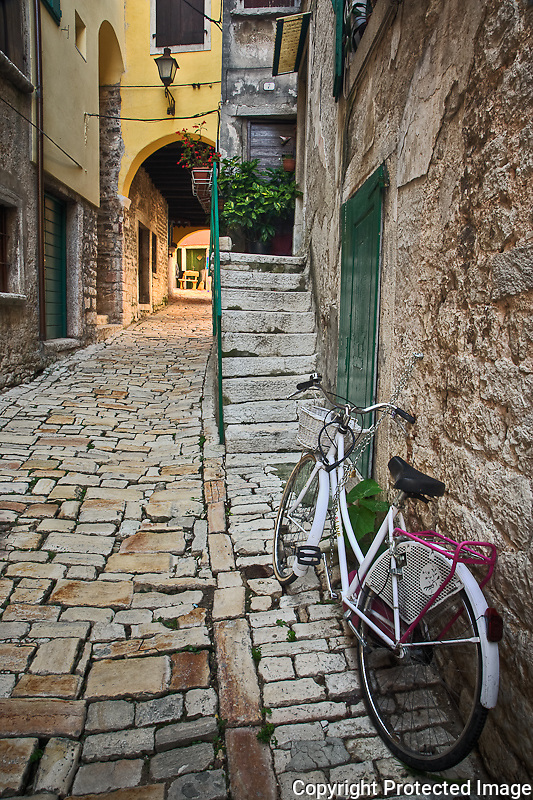 Bicycle and colorful cobblestone alleyway framed by arch, Rovigno, Croatia