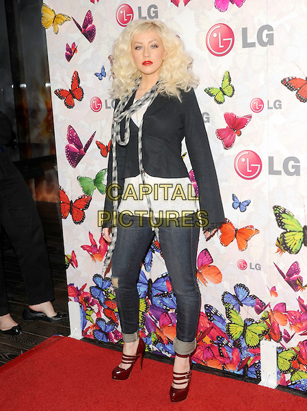 CHRISTINA AGUILERA.The LG Rumorous Night, an exclusive party to celebrate style and introduce the personalized LG Rumor2 backplate designed by fashion icon Heidi Klum held at The Andaz Hotel in West Hollywood, California, USA..April 29th, 2009.full length black jacket jeans denim rolled turned up red maroon triple three strap mary janes shoes platform skinny  scarf curly hair patch .CAP/DVS.©Debbie VanStory/Capital Pictures.
